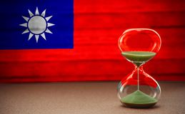 Hourglass on the background of the Taiwan flag, the concept of time and countries, space for text stock image