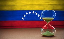 Hourglass on the background of the Venezuela flag, the concept of time and countries, space for text stock photo