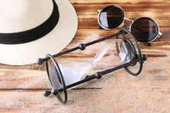 Hourglass with beach hat and sunglasses. On brown wooden table Stock Photos