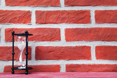 Hourglass. Black hourglass on the brick wall background Stock Images