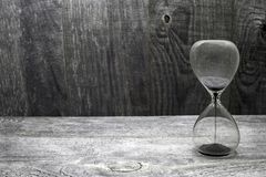 Hourglass with black grains of sand on wooden vintage background stock photo