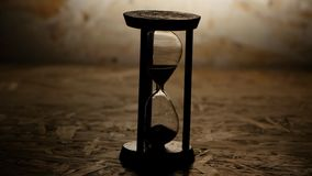Hourglass with black sand. Clock in wooden base. Hourglass with black sand, clock in wooden base, hourglass in a darkened room, sand falls quickly through an stock video footage