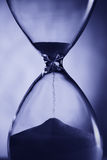 Hourglass in blue light. Stock Image