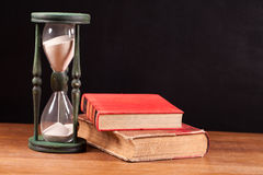 Hourglass and books Royalty Free Stock Photos