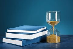 Hourglass with books on table against color background. Time management concept stock image