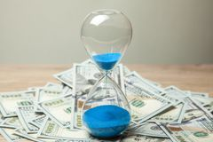 Hourglass and bunch of money dollars of banknotes royalty free stock photo