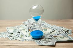 Hourglass and bunch of money dollars of banknotes royalty free stock photography