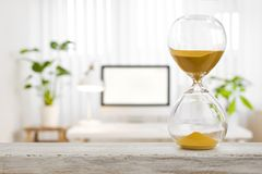 Hourglass business concept. Sand glass in front of blurred office stock photo