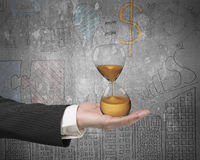 Hourglass in the businessman's hand Stock Photography