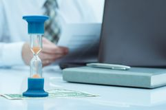 Hourglass. Businessman working in the office in the background. Concept time is money. Royalty Free Stock Photo