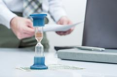 Hourglass. Businessman working in the office in the background. Concept time is money. Hourglass. Businessman working in the office in the background. Concept Royalty Free Stock Images