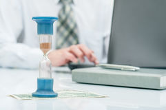 Hourglass. Businessman working in the office in the background. Concept time is money. Stock Photos