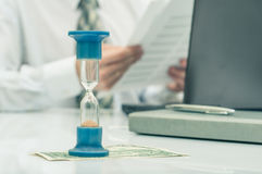 Hourglass. Businessman working in the office in the background. Concept time is money. Stock Photography
