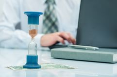 Hourglass. Businessman working in the office in the background. Concept time is money. Hourglass. Businessman working in the office in the background. Concept Stock Photography