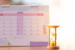 Hourglass on calendar concept for time slipping away for important appointment date. Time passing concept stock image