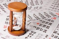 Hourglass on calendar sheets Stock Image