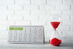 Hourglass with calender stock photography