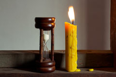 Hourglass and candle Stock Photo
