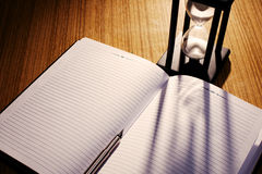 Hourglass Casting Shadow on Notebook with Pen Royalty Free Stock Photo