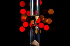 Hourglass in the center. Sand strews down on christmas background, bokeh red christmas lights. Time flow. Time is over royalty free stock photography
