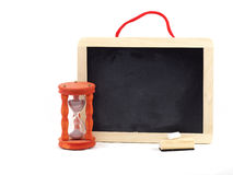 Hourglass and chalkboard. A little wooden and cleaned chalkboard with an handmade hourglass stock images