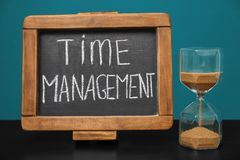 Hourglass and chalkboard with phrase \'Time management\' on table royalty free stock images