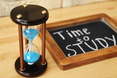 Hourglass and chalkboard on wooden table. Time management concept stock photo