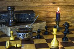 Free Hourglass, Chess Pieces, A Cup Of Tea, A Burning Candle Stand On A Chessboard Stock Image - 148857481