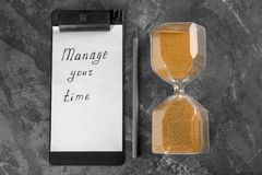 Hourglass with clipboard and pencil on grey textured background. Time management concept stock images