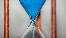 Hourglass closeup reflecting and mirrored on glass table with colorful blue background royalty free stock photography