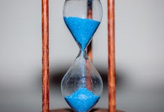 Hourglass closeup reflecting and mirrored on glass table with colorful blue background stock image
