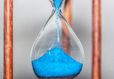 Hourglass closeup reflecting and mirrored on glass table with colorful blue background royalty free stock images