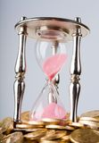 Hourglass and coins Stock Image