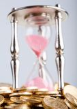 Hourglass and coins Royalty Free Stock Photo