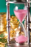 Hourglass and coins Royalty Free Stock Photography