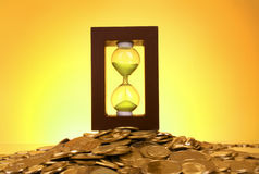 Hourglass and coins Stock Images