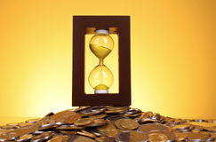 Hourglass and coins Royalty Free Stock Image