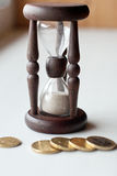 Hourglass and coins Stock Photos