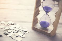 Hourglass with coins. On wooden table Royalty Free Stock Photo