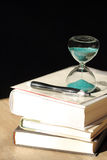 Hourglass countdown with books and a pen Royalty Free Stock Images