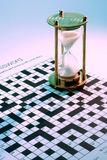Hourglass on Crossword Puzzle. Close Up of Hourglass on Crossword Puzzle Royalty Free Stock Photos