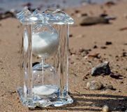Hourglass of crystal on a sandy beach Royalty Free Stock Photos