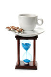Hourglass and a cup of coffee Royalty Free Stock Image