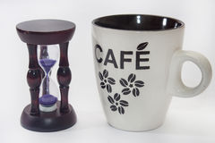 Hourglass and cup of coffee on the white background Stock Photography