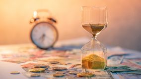 Hourglass and currency on table, Time Investment concept. Sand running through the shape of hourglass on table with banknotes and coins of international currency Royalty Free Stock Photo