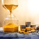 Hourglass and currency on table, Time Investment. Sand running through the shape of hourglass with banknotes and coins stack of international currency on table stock photo