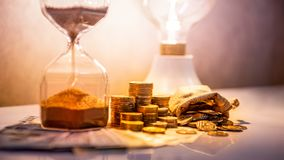 Hourglass and currency on table, Time Investment. Sand running through the shape of hourglass with banknotes and coins stack of international currency on table royalty free stock photography