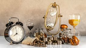 Hourglass and currency on table, Time Investment royalty free stock photo