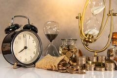 Hourglass and currency on table, Time Investment royalty free stock photography