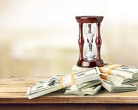 Hourglass and Currency Stock Photography